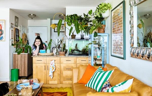 Wypełniona roślinami otwarta przestrzeń z kuchenną wyspą, akwarium, sofą, poduszkami i stolikiem kawowym oraz dekoracją ścienną.