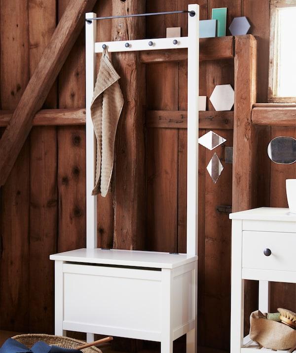 Wysoka biała ława ze schowkiem oraz drążkiem i haczykami na górze oraz miejscem do siedzenia.