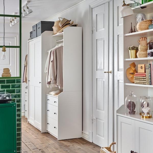 Wysoka szafka, zamknięta szafa i dwie otwarte szafy z serii HAUGA tworzące spójny wystrój w obu sąsiednich pomieszczeniach.