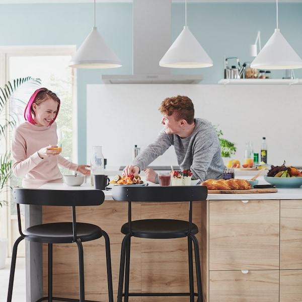 Wyspa kuchenna z krzesłami narowymi i stojcymi przy niej osobami.