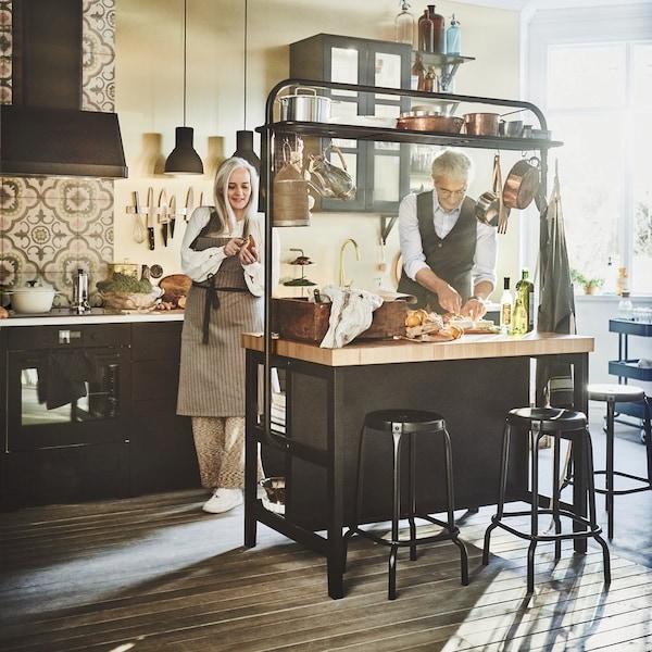 Wyspa VADHOLMA stojąca w kuchni. Rodziana gotująca przy niej.
