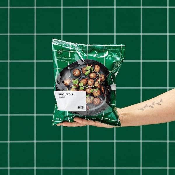 يد ممدودة تحمل عبوة غير مفتوحة من الكرات النباتيةHUVUDROLL. حائط ببلاطات خضراء في الخلفية.