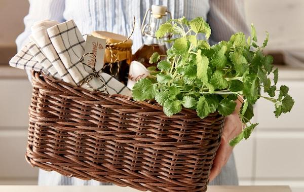 يدان تعرضان سلة GABBIG مليئة بمناديل الشاي الملفوفة بأشرطة، وأطعمة محفوظة في المنزل في مرطبانات زجاجية وأعشاب طازجة.