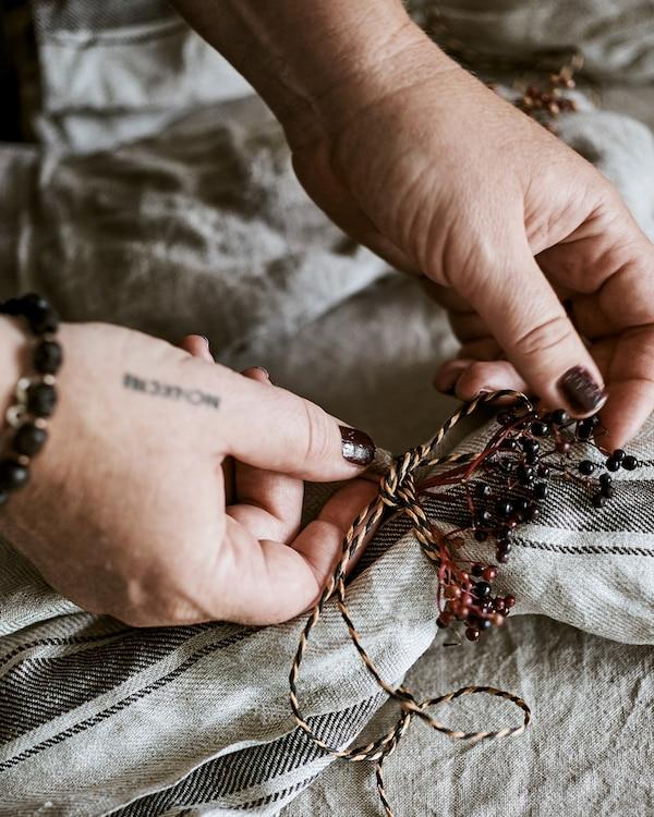 يدان تقومان بربط عقدة زخرفية مصنوعة من الخيوط المجدولة باللون الطبيعي والأسود وتوت بري بلون الخوخ حول المنديل.