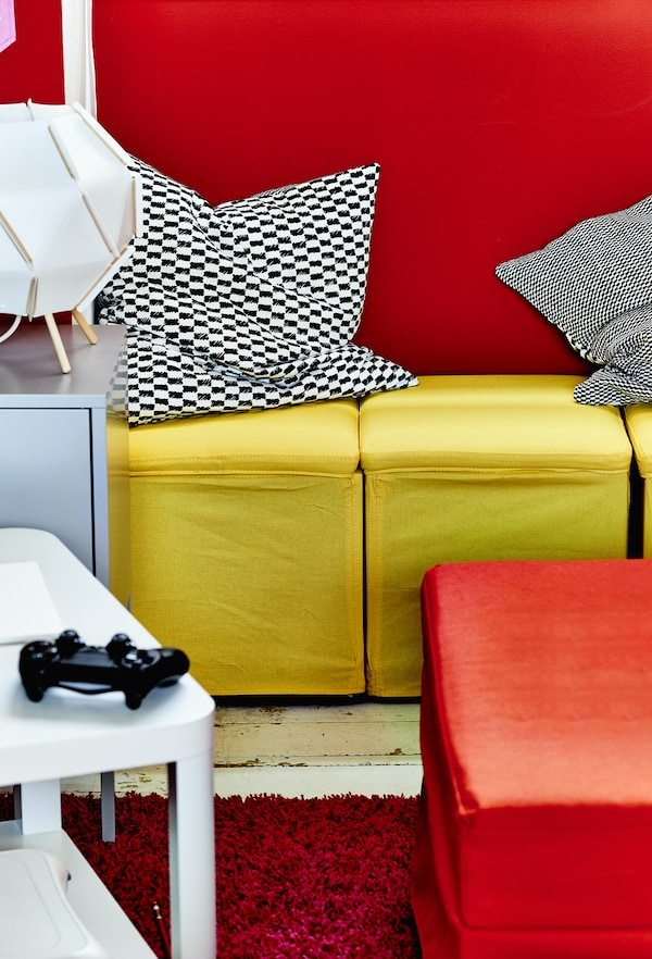Yellow footstools against a red wall.