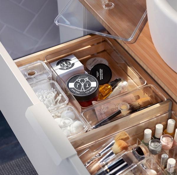 Yhdistelmä läpinäkyviä GODMORGON-säilytyslaatikoita, jotka on täytetty puiseen laatikkoon sijoitetuilla kylpyhuoneen välttämättömyystarvikkeilla.