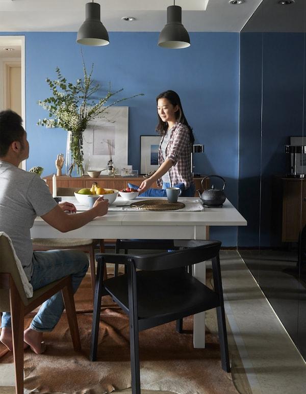 Yiqing stellt im Esszimmer Essen auf den Tisch. Derrick sitzt am Tisch.