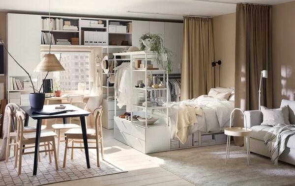 Yksiö, jossa on valkoinen PLATSA säilytysyhdistelmä ja sängynrunko, siro ruokapöytä, vaaleanharmaa sohva ja beiget verhot.