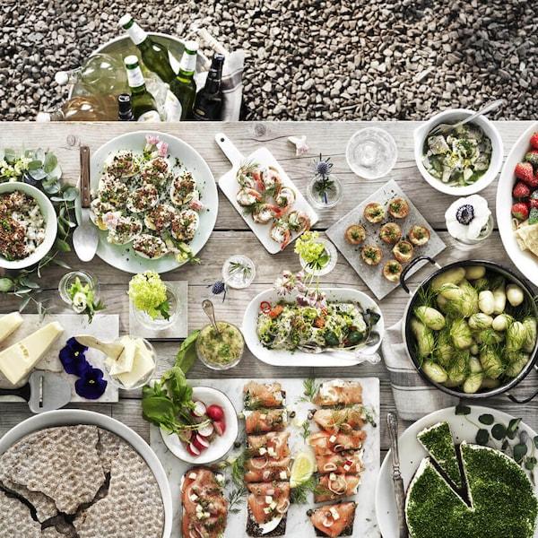 Ylhäältä kuvattuna puupöytä, jolle on katettu kesäinen buffet: salaattia, kalaherkkuja, leipää, krustadeja, mansikoita ja muuta.