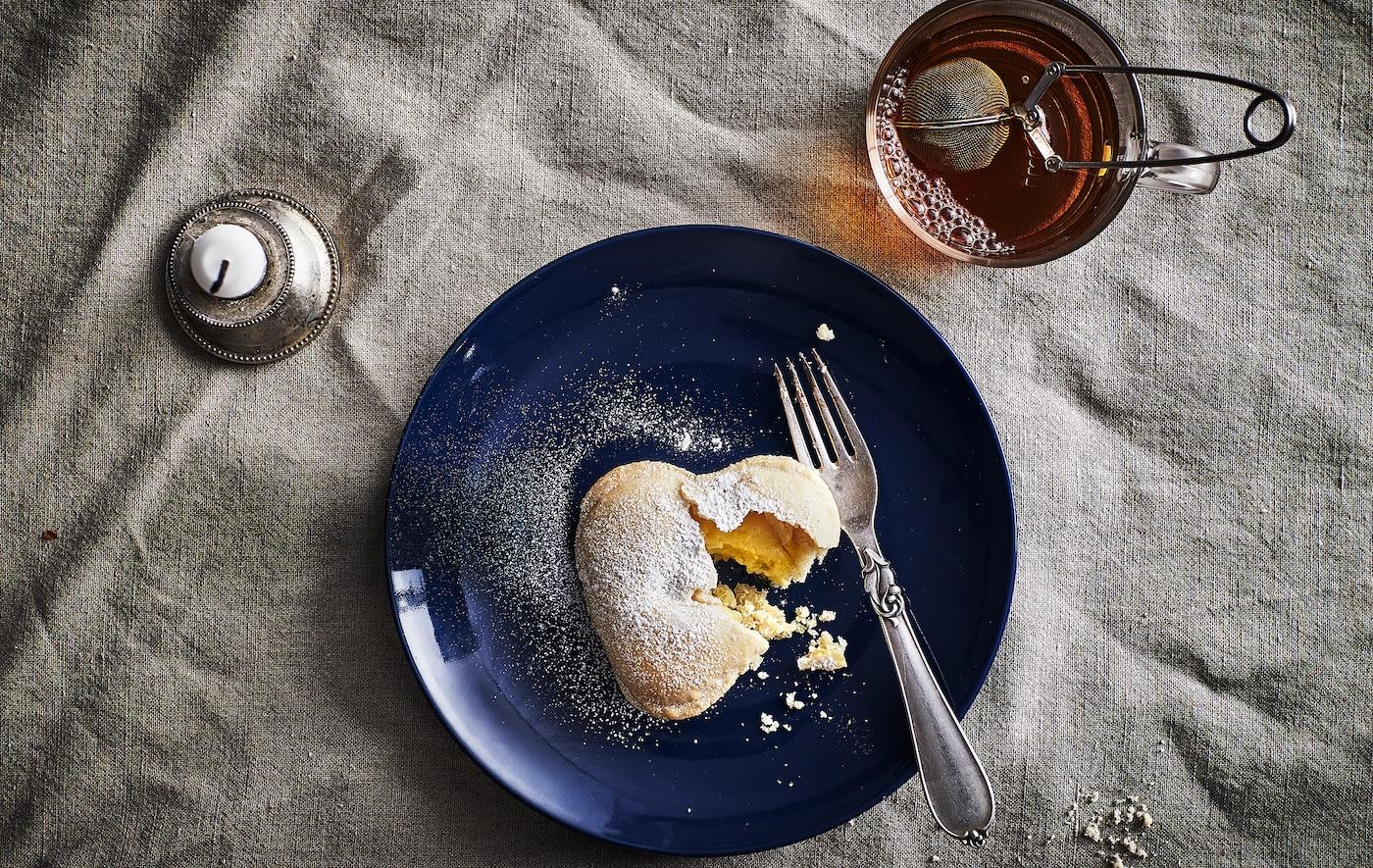 Ylhäältä kuvattuna sydämenmuotoinen leivos ja haarukka tummansinisellä lautasella, teemuki ja kynttilä.
