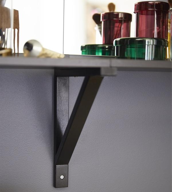يمكنك اتخاذ نهج غير تقليدي بالنسبة لأثاث غرفة النوم الداكن وإنشاء طاولة الزينة الخاصة بك. إلى جانب دولاب الملابس أو الخزانة، ضع رف وحامل جداري EKBY LAIVA/EKBY VALTER باللون الأسود-البني.