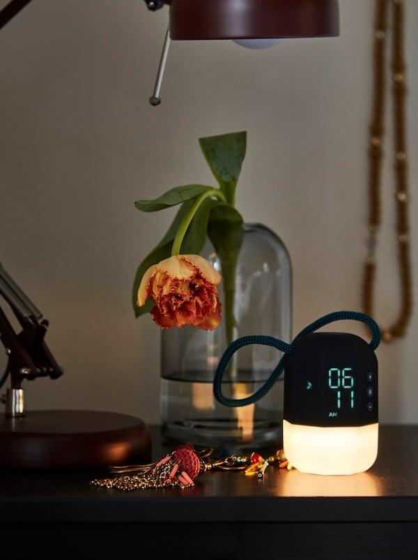 Yöpöydällä herätyskello, jonka sarastusvalo loistaa himmeää valoa, sekä lasimaljakko jossa oranssi tulppaani.