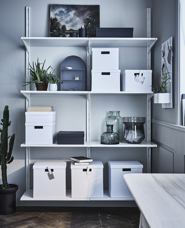You can get your storage to blend in by adding touches of colours and patterns that match the rest of your deco. We used an open customisable shelving unit and added boxes with lids in the same tone for a uniform feel. Just write what's inside on clips so you can easily find your stuff. Store receipts in a minimal glass vase (these three come as a set and stack together when they are not needed).