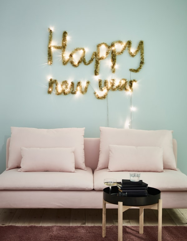 You can make new year wall decorations from holiday decor like SÄRDAL battery-operated LED light chains and gold garland from IKEA. Use the lights to pin up your new year mantra. Wrap garland around the lights so the message shines all the time.