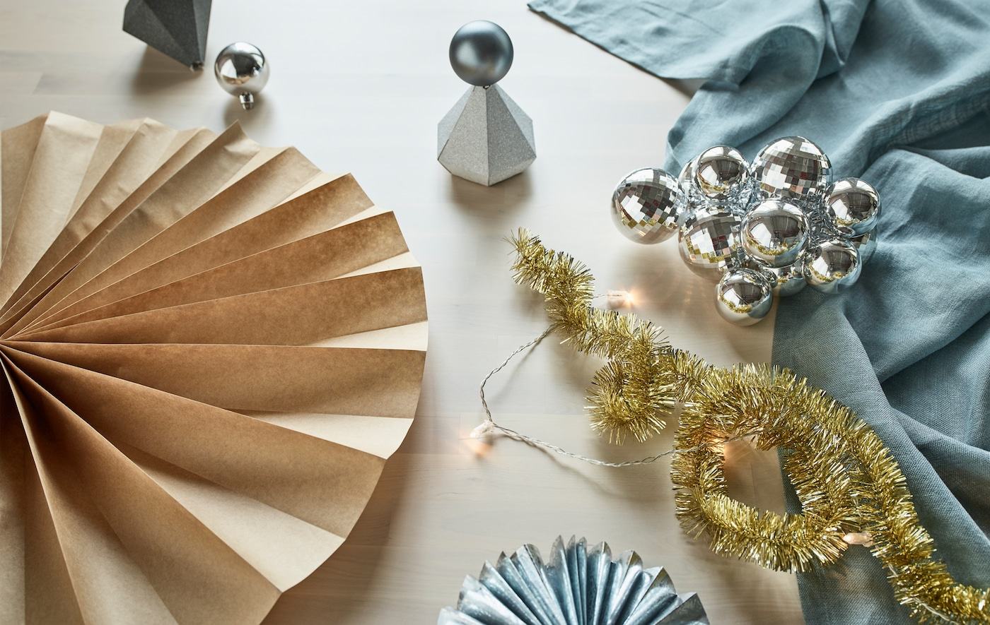 You can make recycled party decorations from IKEA holiday products like VINTER 2017 gold garland, silver gift boxes and baubles and wrapping paper. Turn them into wall decor, table toppers and paper rosettes.