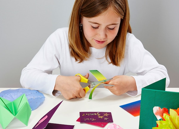 young girl sitting at a table, cutting colored paper with scissors, surrounded by other colored paper
