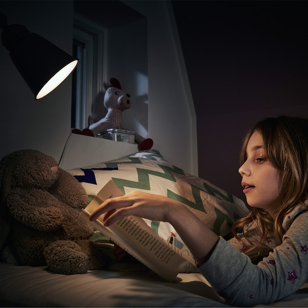 Young girl wearing gray sweater lying in bed at night reading a book under a light.