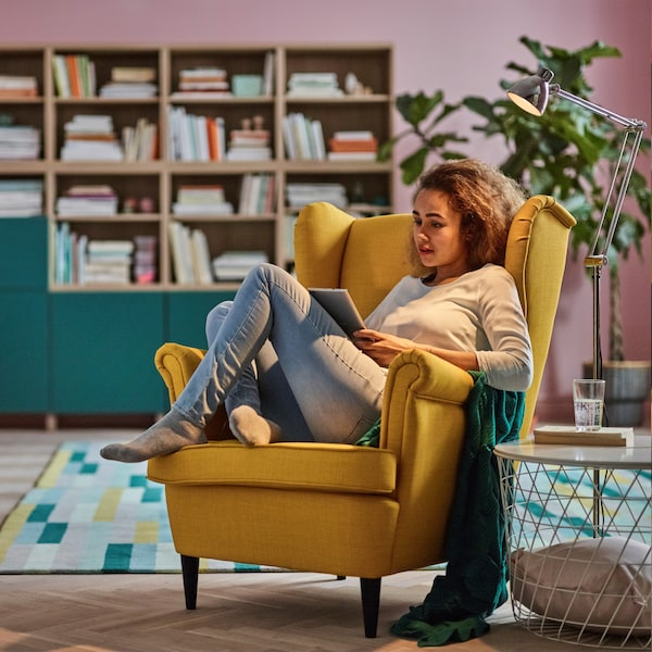 Young woman sitting on a yellow Strandmon armchair.