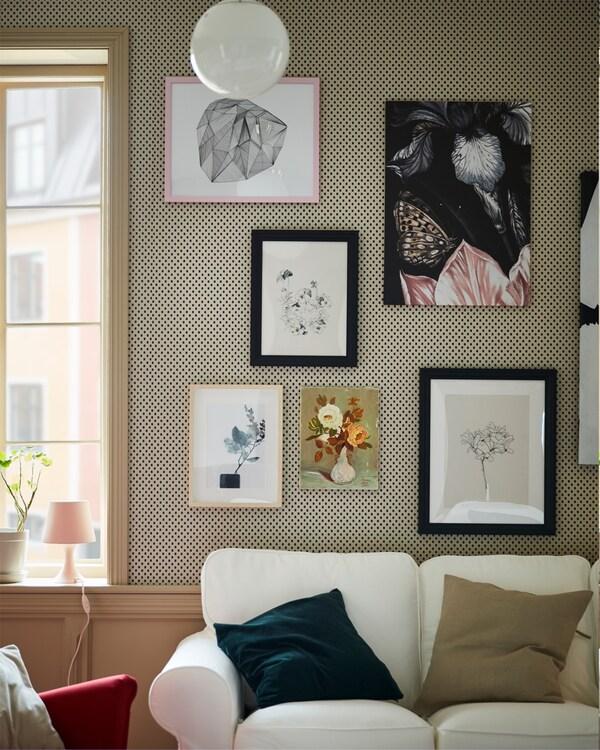 يتم دمج الإطارات الملونة باللون الأسود مع المزيد من الإطارات لإنشاء جدار صور خلف أريكة EKTORP بيضاء.