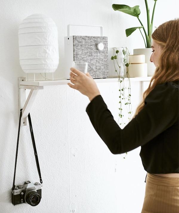Yvet coloca un vaso en una balda con una lámpara, un altavoz y plantas.