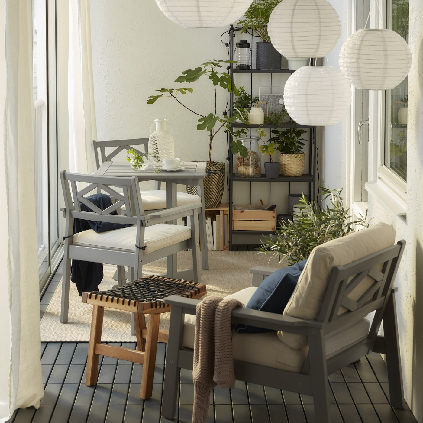 Zabudowany balkon z szarymi meblami BONDHOLMEN, okrągłymi lampami wiszącymi, beżowym dywanem, białymi zasłonami i licznymi roślinami.