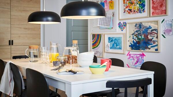 Zajtrk, postrežen na beli EKEDALEN mizi s črnimi stoli in dvema visečima svetilkama, zadaj na steni pa otroške risbe.