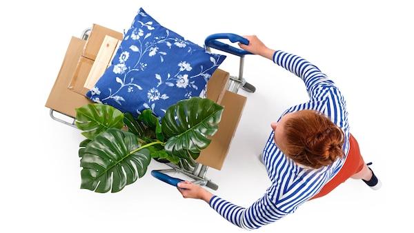 Zákazníčka si z IKEA výdajného miesta odváža vozík plne naložený výrobkami.
