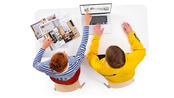 Zákazníčka spolu so zamestnancom IKEA plánujú zariadenie v obývačke nad počítačom a katalógom IKEA.