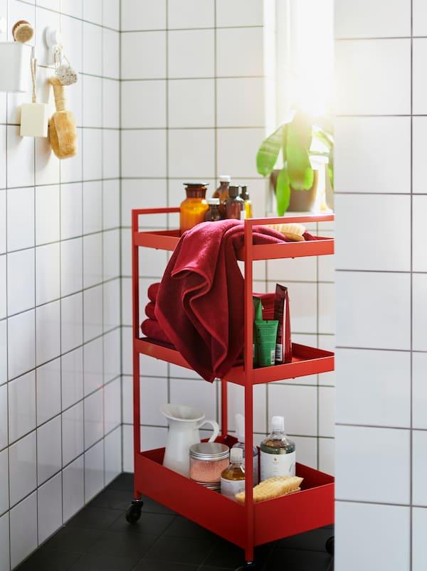 Załadowany akcesoriami czerwony wózek NISSAFORS ustawiony w łazience wyłożonej białymi płytkami i umeblowanej czerwono-białymi modułami ENHET.