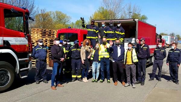 Zaměstnanci IKEA před hasičským autem a dodávkou.