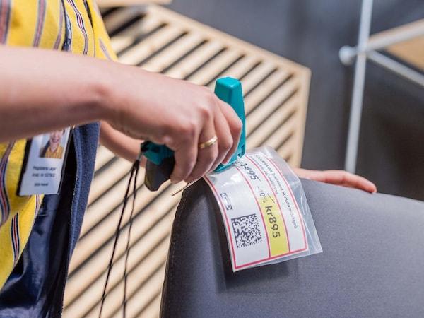 Zaměstnanec IKEA připevňující cenovku na zlevněné zboží.
