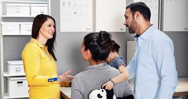 Zaměstnankyně IKEA v žluté uniformě vysvětluje páru s dítětem bližší informace o službách IKEA.