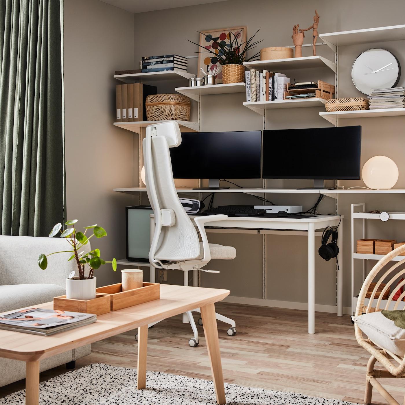 Zamocowany do ściany regał z dwoma monitorami komputera i książkami, stolik kawowy wykończony okleiną jesionową i biało-beżowe krzesło biurowe.