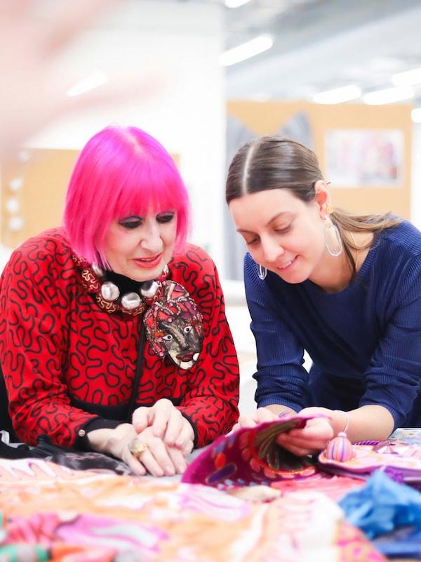 Zandra Rhodes und IKEA Designerin Paulin Machado schauen sich auf einem Tisch farbenfrohe Textilien an.