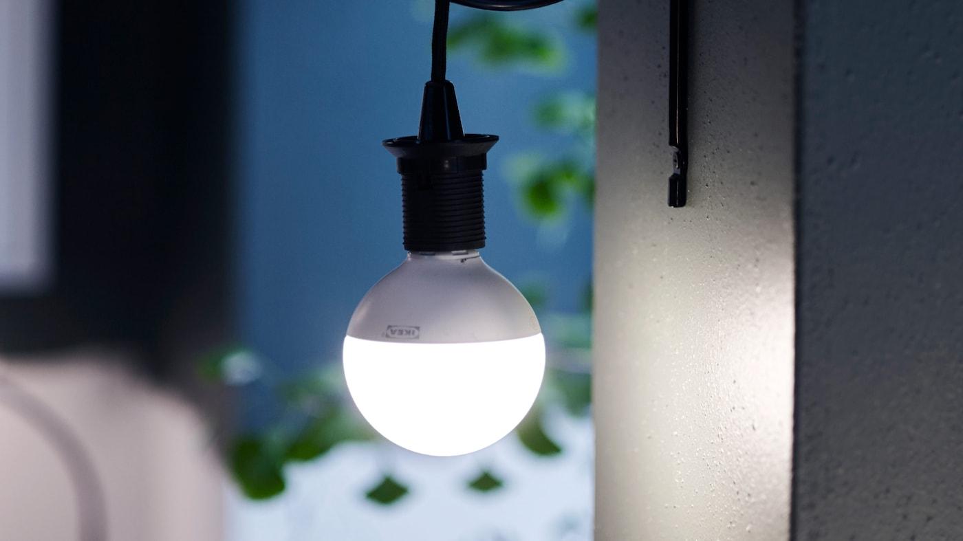 Żarówka LED zawieszona na czarnym przewodzie na tle ciemnoniebieskiej ściany.