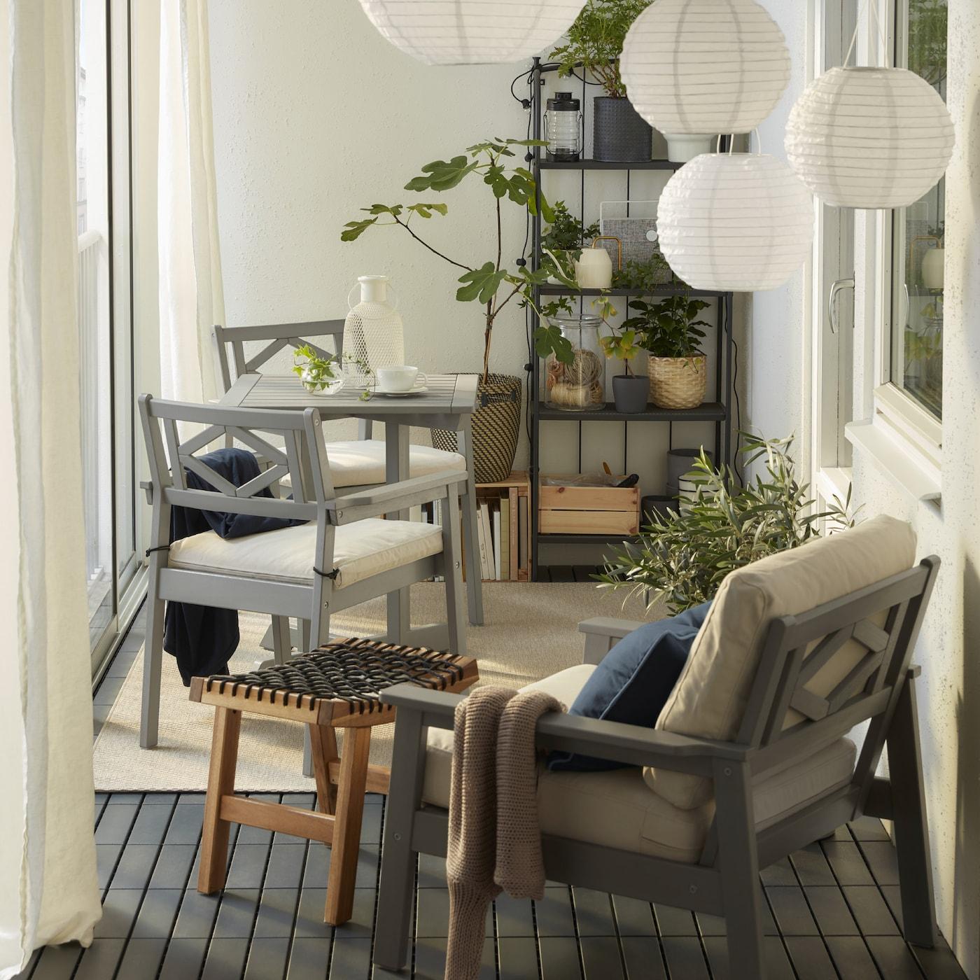 Zárt erkély, szürke BONDHOLMEN bútorral, kerek függőlámpákkal, bézs szőnyeggel, fehér függönyökkel, és sok zöld növénnyel.