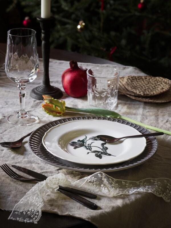 Zastawiony w tradycyjnym stylu stół z białym talerzem UPPLAGA ustawionym na większym, niebieskim talerzu.
