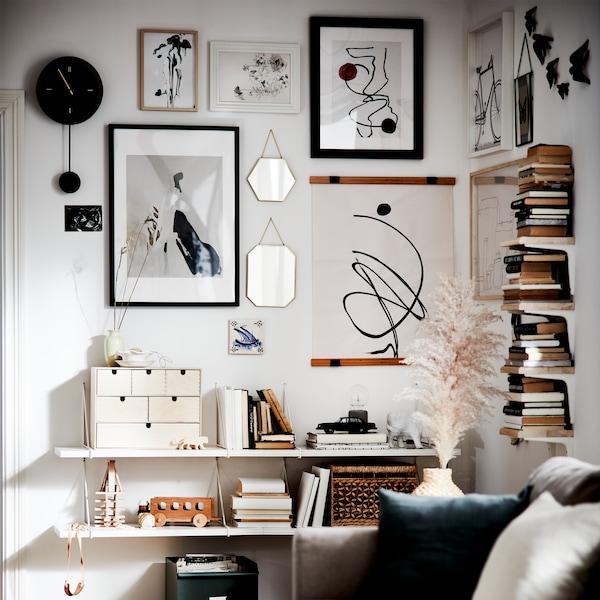 Zawieszone na ścianach lustra w ramkach w kolorze złotym, oprawione plakaty różnej wielkości, białe półki i pionowe półeczki tworzące mały regał na książki.