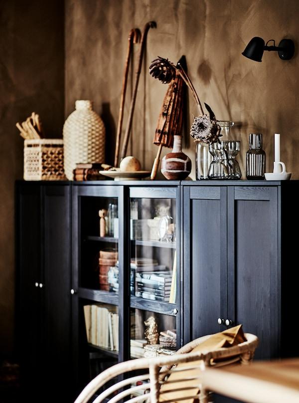 زاوية في غرفة جلوس مع خزانة HAVSTA داكنة عريضة مملوءة ومغطاة بقطع فنية من خامات طبيعية.