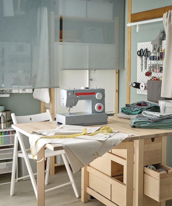 زاوية في غرفة مهيأة كمحطة للخياطة مع طاولة NORDEN محملة بآلة الخياطة والمنسوجات والاكسسوارات.