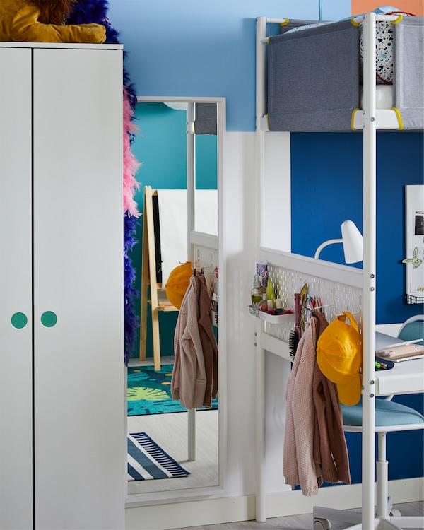 زاوية للزينة تشمل مرآة بيضاء ولوحة مشابك بيضاء مع إكسسوارات.
