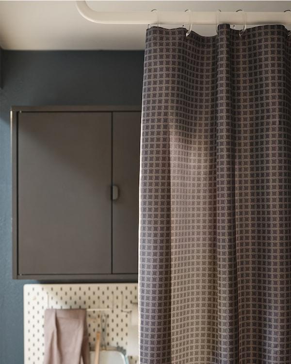 زاوية شرفة مع خزانة مثبتة على الحائط وتخزين لوح مشابك، كلها نصف مغطاة بستارة دوش.