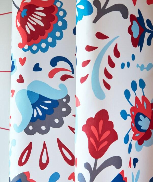 Zbliżenie na część zasłony prysznicowej w jaskrawych kolorach i ozdobionej tradycyjnym szwedzkim wzorem kurbits.