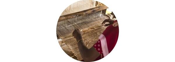 Zbliżenie na kobietę tkającą dywan na krośnie.