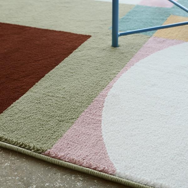 Zbliżenie na miękki dywan z krótkim włosiem STENMÄTARE z utrzymanym w stylistyce Bauhausu wzorem w odcieniach różowego, miętowego, niebieskiego, żółtego i ciemnoczerwonego.