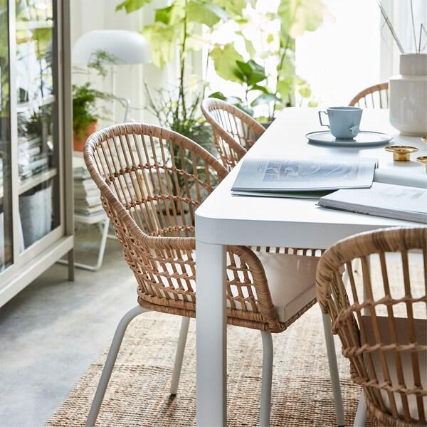 Zbliżenie na wyplatane krzesło rattanowe IKEA NILSOVE obok białego stołu TINGBY, na którym stoją filiżanki z kawą i książki.