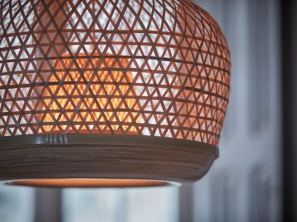 Zbliżenie na zapaloną lampę wiszącą MISTERHULT tkaną ręcznie z lekkiego, naturalnego bambusa.