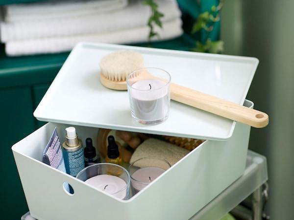 Zelená krabička s vrchnákom, ktorá skrýva kúpeľňové doplnky - sviečky, kefu na vlasy, sprej.
