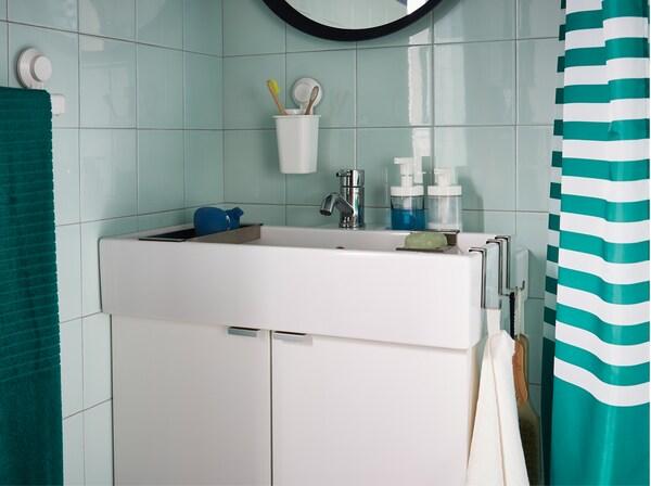 Zelená kúpeľňa s bielou skrinkou s umývadlom a uterákmi, mydlom a zubnými kefkami.