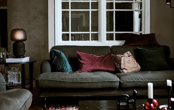 Zelená pohovka s vankúšmi v obývacej izbe s konferenčným stolíkom so stolovou lampou a perzským kobercom.